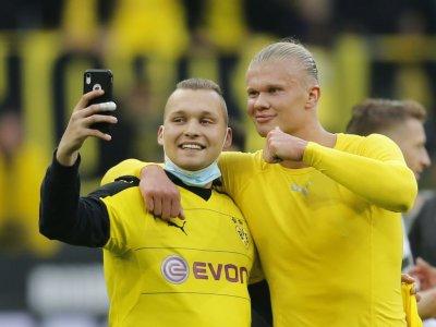Haaland celebrates with fan after sending Dortmund top