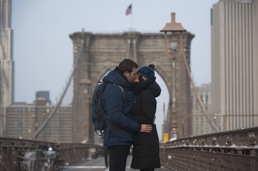 A couple stops to kiss while walking across a bridge. — Reuters pic