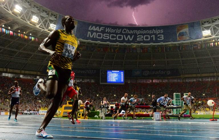 """有着""""闪电""""外号的博尔特,在2013年莫斯科的田径世锦赛百米决赛,与闪电落下的同时""""抵达""""终点,让这张照片成为经典。-法新社-"""