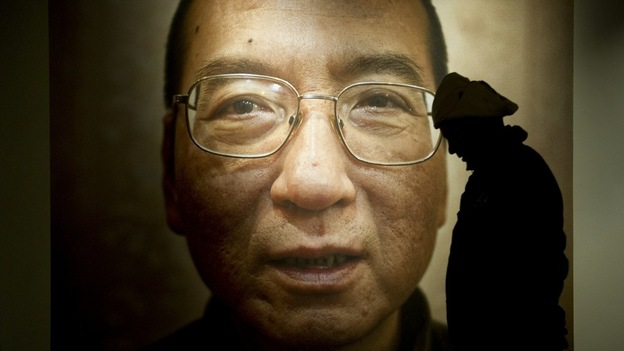 A man walks in front of a poster of Liu Xiaobo. — AFP pic