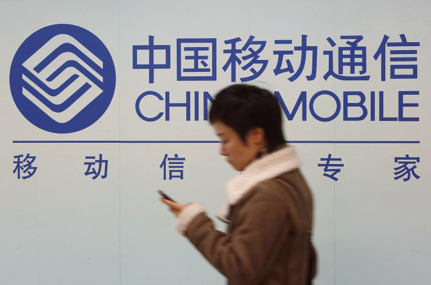 A woman looks at the screen of her mobile phone while walking past a China Mobile sign in downtown Shanghai. — Reuters pic