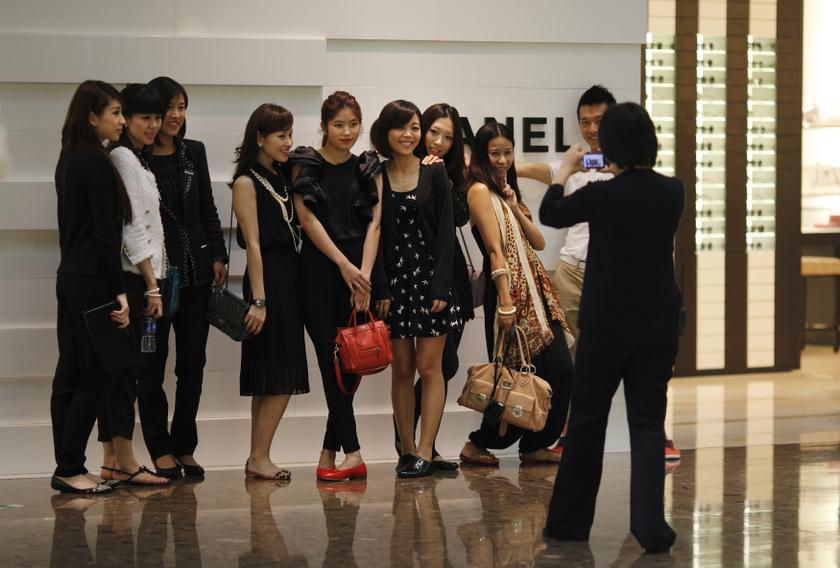 Shoppers pose for a picture in front of a Chanel luxury boutique at the IFC Mall in Shanghai, in this June 4, 2012 file picture. — Reuters pic