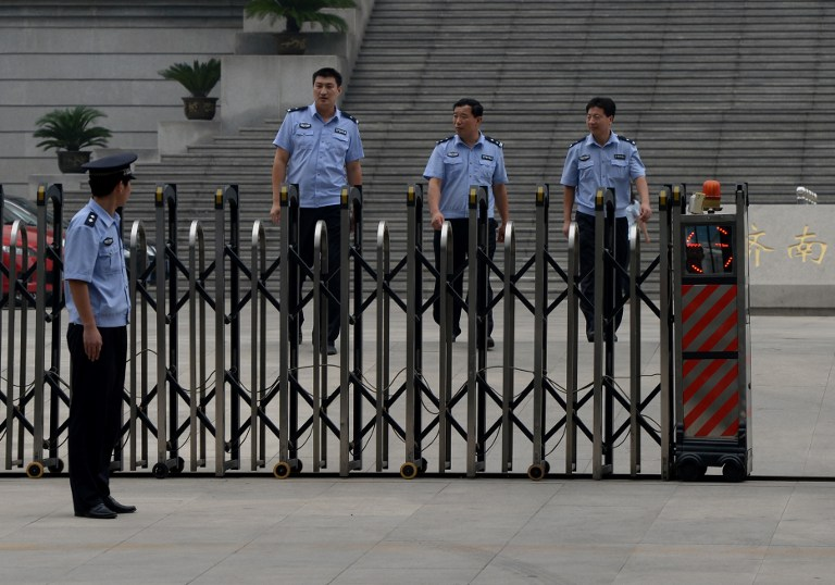 Chinese police patrol outside the Intermediate People's Court, Jinan, Shandong Province on July 25, 2013. — Reuters pic