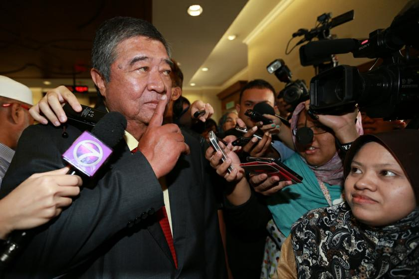 Tun Dr Ling Liong Sik, putting a finger to his lips, declined to comment after the court acquitted him from the cheating charges over the PKFZ land purchase. October 25, 2013. — Picture by Saw Siow Feng