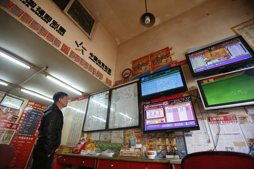 A customer looks at screens showing lottery information at a lottery ticket store in Shanghai, December 29, 2013. — Reuters pic