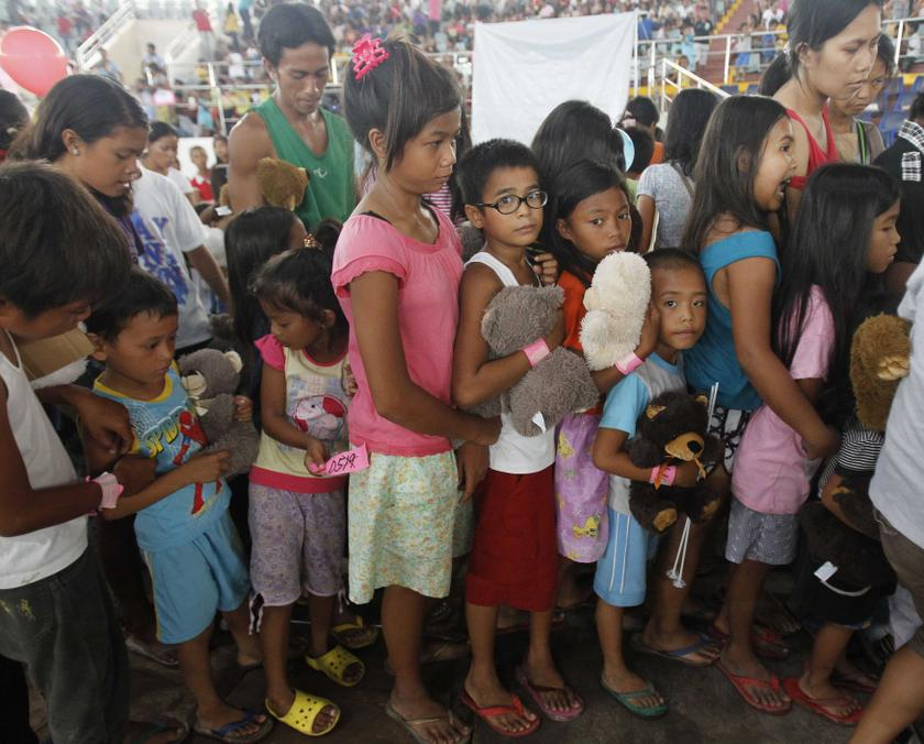 File picture of children queuing during a gift giving activity inside a astrodome at Tacloban city, Philippines. Almost 2,000 people, mostly schoolchildren, have fallen ill after eating contaminated fruit-flavoured candy in the Philippines. — Reuters pic