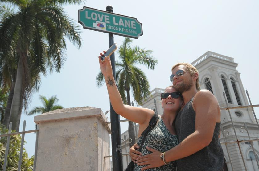 Tourists Tom and Kate taking their portrait at Love Lane, Penang for their valentine memory during their visit to here, February 14, 2014. Jakim has consistently opposed the celebration of Valentine's Day among Muslims, claiming it possesses Christian elements.— Picture by K.E. Ooi