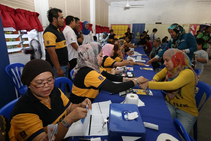 People exchange vouchers for cash Bantuan Rakyat 1Malaysia (BR1M) counter in Kuala Lumpur. — Picture by Saw Siow Feng