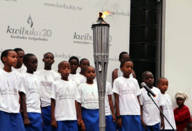 Children stand around the 'flame of remembrance' on its arrival in Rubavu. — AFP pic