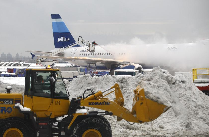 A worker de-ices an airplane sitting at a gate near terminal C as a man in a tractor removes snow from the tarmac at LaGuardia Airport in the Queens borough of New York in this file photo. — Reuters pic