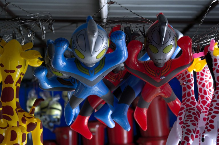 Plastic toys of Japanese animation superhero 'Ultraman' hang from the ceiling of a shop for sale in Karak, some 80 kilometres east of Kuala Lumpur on March 7, 2014. — AFP pic