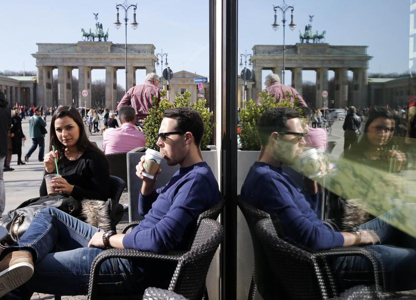 Tourists are reflected in a coffee shop window as they sit outside enjoying the sunshine in front of the Brandenburg Gate in Berlin March 20, 2014. Evidence from new European research suggests that a higher coffee consumption can reduce the risk of death.— Reuters pic