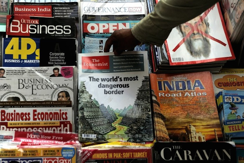 An Indian magazine vendor arranges a censored issue of the Economist magazine at a road-side stall in New Delhi on May 24, 2011. — AFP pic