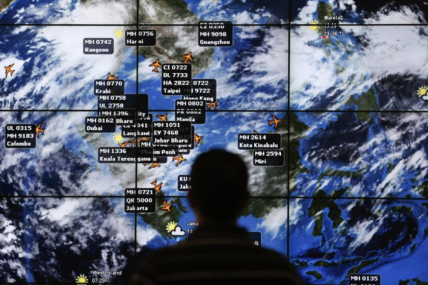 A man watches a large screen showing different flights at the departure hall of Kuala Lumpur International Airport March 13, 2014. — Reuters pic