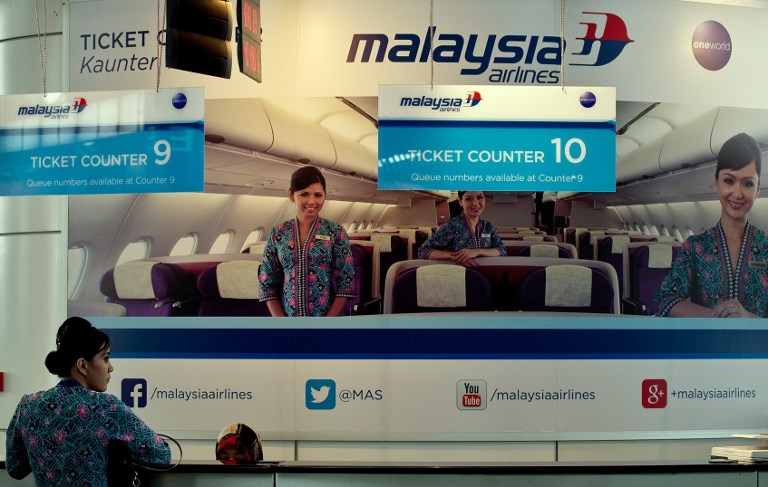 A Malaysia Airlines crew member stands at an empty ticket counter at the Kuala Lumpur International Airport in Sepang March 8, 2014. — AFP pic