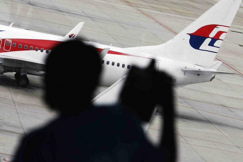 A passenger takes pictures of a Malaysia Airlines plane at the Kuala Lumpur International Airport March 16, 2014. — Reuters pic