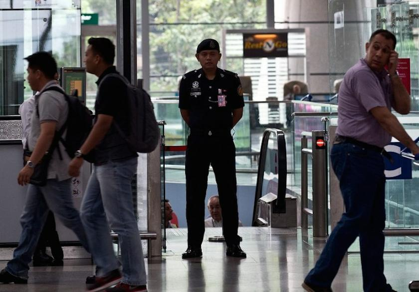 An auxiliary policeman at the KLIA departure hall was seen checking thoroughly passengers' documents and flight details before allowing them to proceed to the Immigration counters. — AFP pic