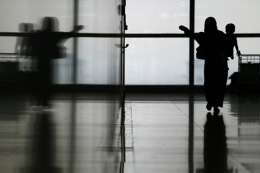 A woman carries her child through the departure hall of the Kuala Lumpur International Airport March 11, 2014.— Reuters pic