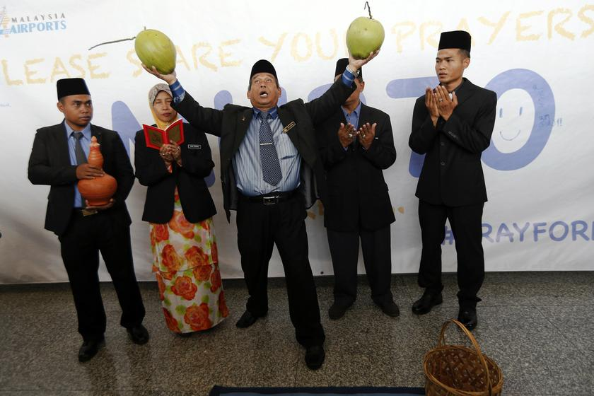 Ibrahim Mat Zin (centre), a local well-known 'bomoh', holds two coconuts as he performs a ritual to help finding the missing Malaysia Airlines MH370 at Kuala Lumpur International Airport March 12, 2014. — Reuters pic