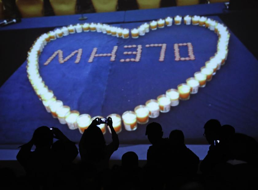 Relatives of passengers aboard Malaysia Airlines MH370 takes picture of a screen while a slideshow is played at the Lido Hotel in Beijing March 27, 2014. — Reuters pic