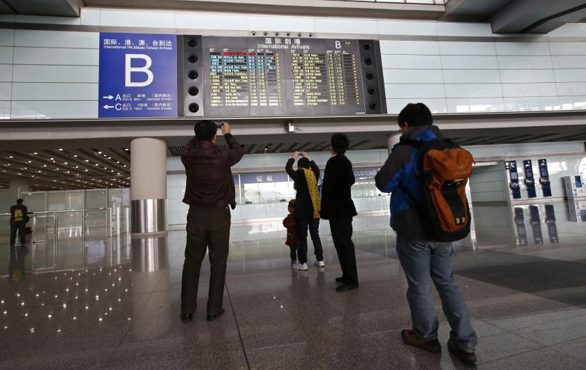 People take pictures of a flight information board displaying the Scheduled Time of Arrival of Malaysia Airlines flight MH370 (top, in red) at the Beijing Capital International Airport in Beijing, March 8, 2014.— Reuters pic