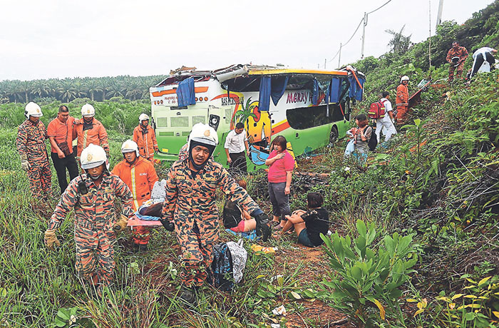 File picture of Fire and Rescue Department personnel helping passengers after a double-decker bus crashed into a ravine at Km70 of the Kuantan-Segamat highway near Pekan, April 20, 2014. A collision between a car and a bus caused both vehicles to plunge into a ravine in Sabah today. — Malay Mail pic