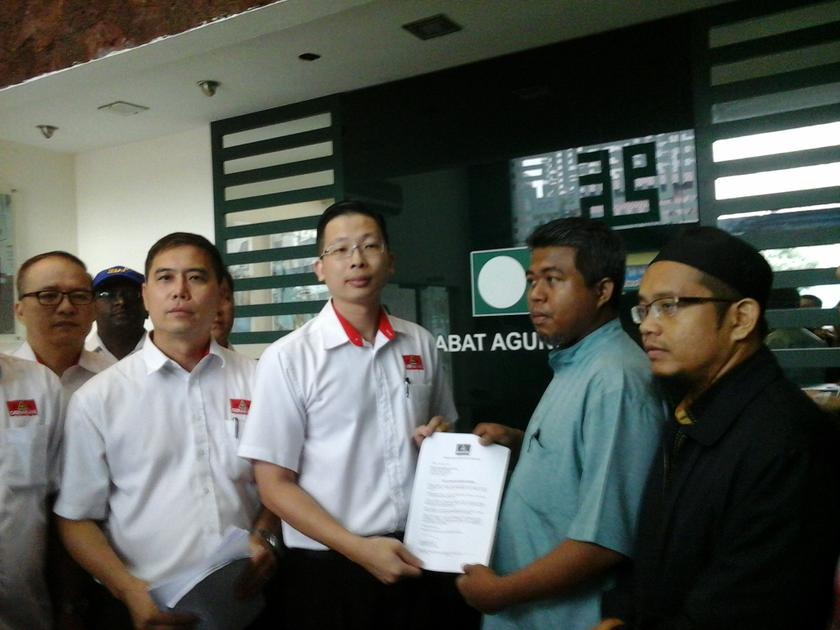 Gerakan youth chief Tan Keng Liang handing the legal notice to a representative of PAS Youth at the party's Kuala Lumpur headquarters, April 24, 2014. — Picture by Yap Tzu Ging