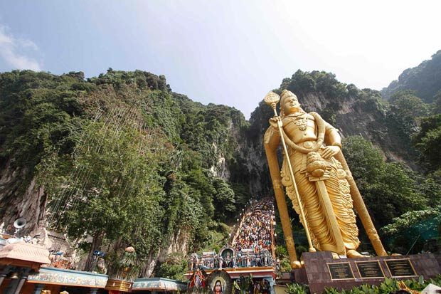 Hindu devotees climb the a 272-step staircase next to the giant statue of Lord Murugan to the Batu Caves temple to complete their pilgrimage during Thaipusam festival outside Kuala Lumpur. — Reuters pic
