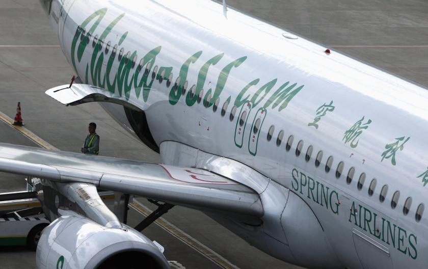 An employee of Spring Airlines stands next to an Airbus A320 aircraft at Hongqiao Airport in Shanghai in this July 6, 2012 file photo. — Reuters pic
