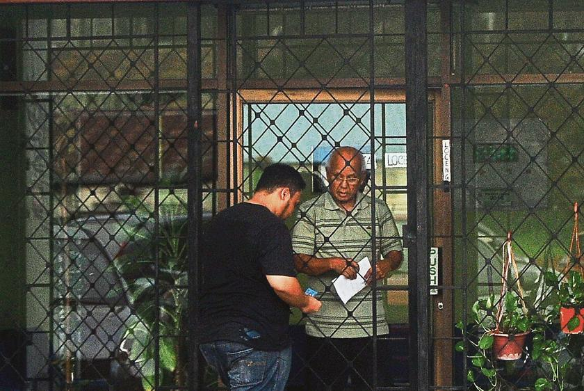 One of the reporters paying for his MC at Klinik Rakyat. — Picture by The Malay Mail