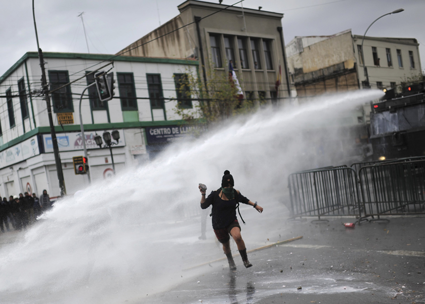 A protester is hit by a jet of water during a clash with riot policemen during an anti-government rally as Chile's president delivers a speech inside the national Congress at Valparaiso city, May 21, 2014. — Reuters pic