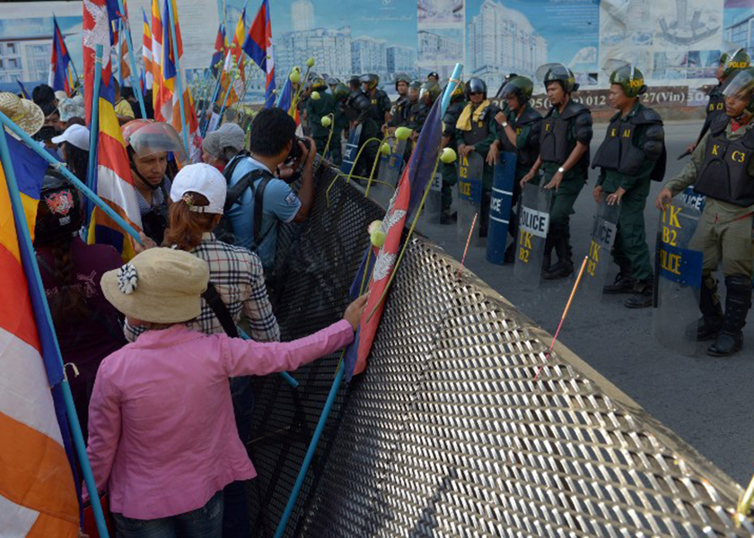 Cambodian rights activists stand next to a barricade in front of police officials during a protest near the Phnom Penh Municipal Court, May 30, 2014. — AFP pic