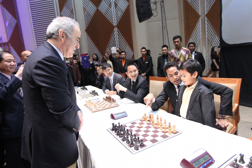 Kasparov at the Charity Simultaneous Exhibition with Khairy Jamaluddin helping a young talent.