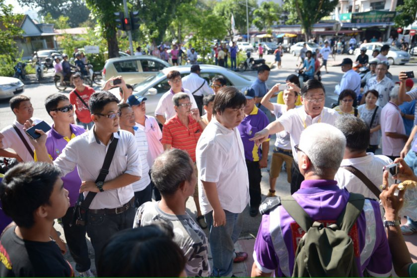 PCM candidate Huan Cheng Guan (right, with arm outstretched) confronts DAP members outside a polling centre in Paya Terubong May 25, 2014. — Picture by K.E. Ooi