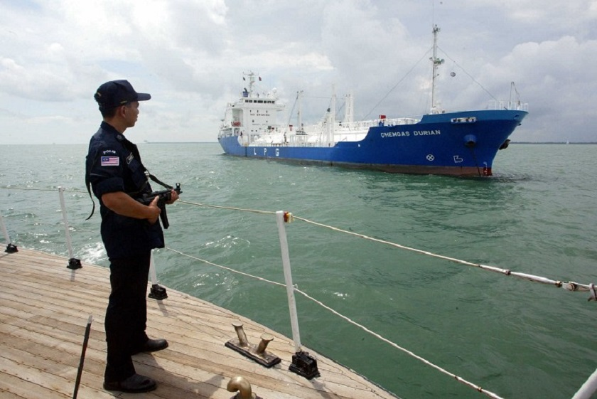 This file picture shows an armed marine policeman standing guard on the deck of his patrol boat while patrolling past a tanker in the Straits of Malacca. Pirates hijacked Malaysia-registered tanker MT Budi Mesra Dua last Saturday off Bintulu in the oil-rich Sarawak state as the ship sailed from neighbouring Singapore. — AFP pic