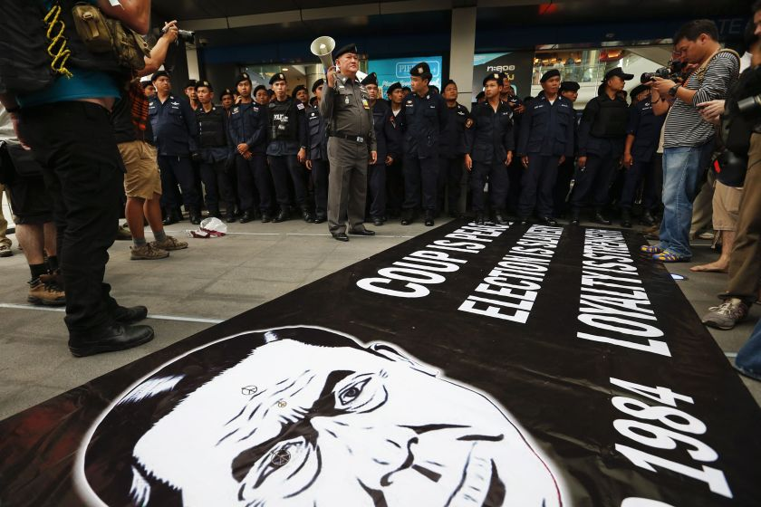 Policemen arrive to remove a banner with a drawing of the army chief and coup leader General Prayuth Chan-ocha left by anti-coup protesters at a shopping mall in Bangkok June 1, 2014. — Reuters pic