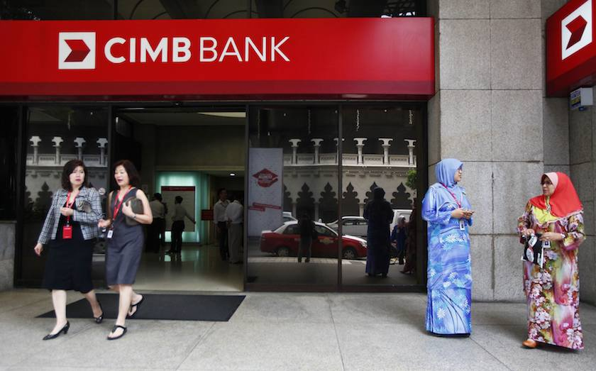 People are seen in front of a CIMB bank office in Kuala Lumpur in this February 25, 2014 file photo. — Reuters pic