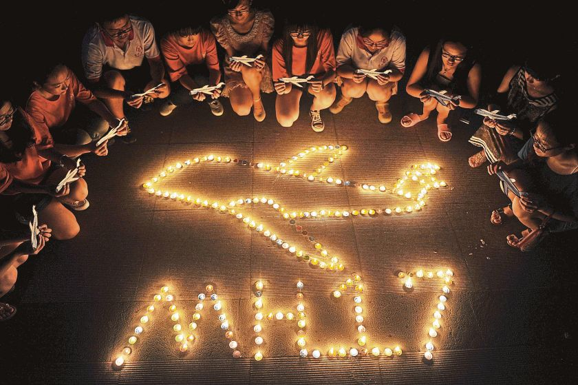 College students gather around candles forming the shape of an airplane, during a candlelight vigil for victims of the downed Malaysia Airlines Flight MH17, at a university in Yangzhou, Jiangsu province July 19, 2014. — Picture by Reuters
