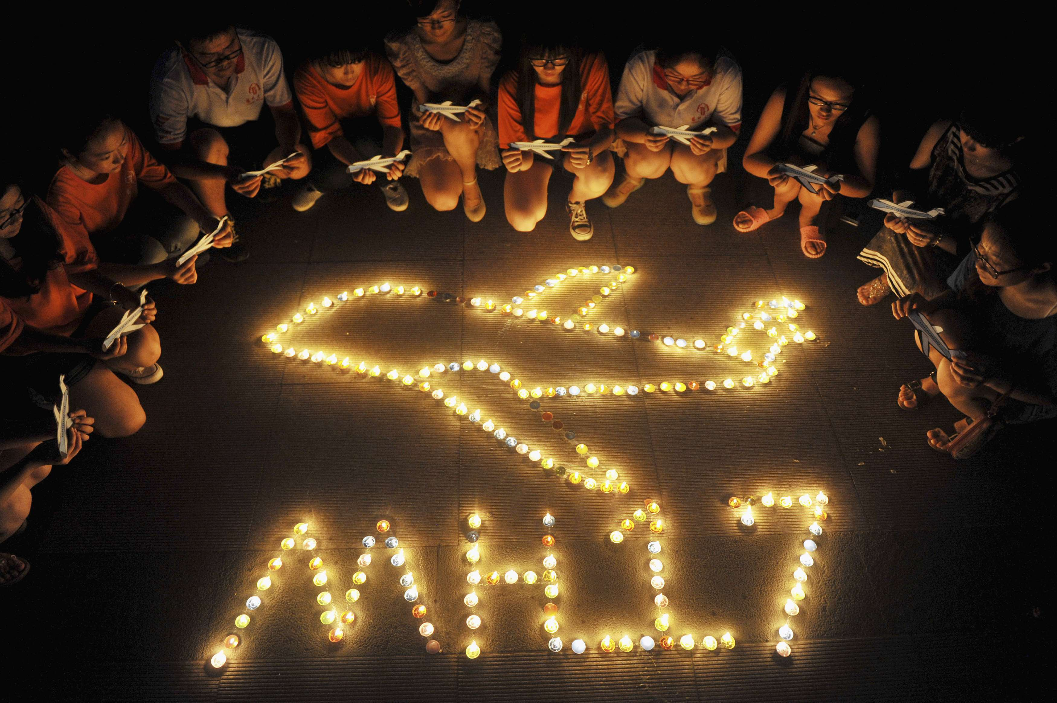 College students gather around candles forming the shape of an airplane, during a candlelight vigil for victims of the downed Malaysia Airlines Flight MH17, at a university in Yangzhou, Jiangsu province July 19, 2014. — Reuters pic