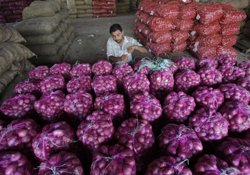 A worker packs onion bags at a vegetable and fruit wholesale market in the northern Indian city of Chandigarh July 9, 2014. — Reuters pic