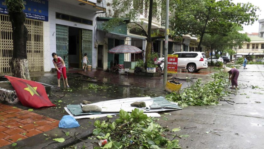 Shop owners clear felled tree branches from the street after heavy rainfall from Typhoon Rammasun in Mong Cai July 19, 2014. ― Reuters pic