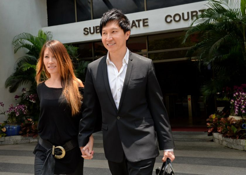 City Harvest Church founder Kong Hee with his pop-singer wife Ho Yeow Sun outside the district courts in Singapore in August 2013. — AFP pic