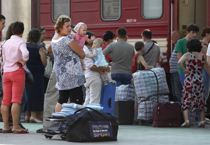 Passengers wait before boarding a train terminating in Moscow, at a railway station in the eastern Ukrainian city of Donetsk, August 10, 2014. — Reuters pic