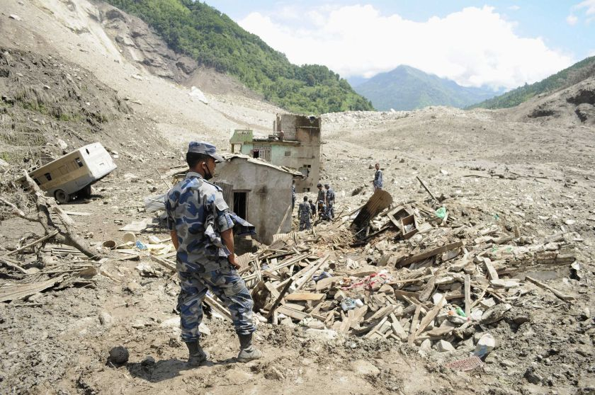 A rescue team from the Armed Police Force stands near damaged houses in the landslide area in Sindhupalchowk district, August 2, 2014. — Reuters pic