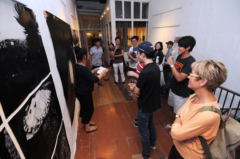 Nozomi iijima showing visitors her exhibit, The Hidden Blood, which is part of the Japanese Photography Showcase at China House. — picture by K.E.Ooi