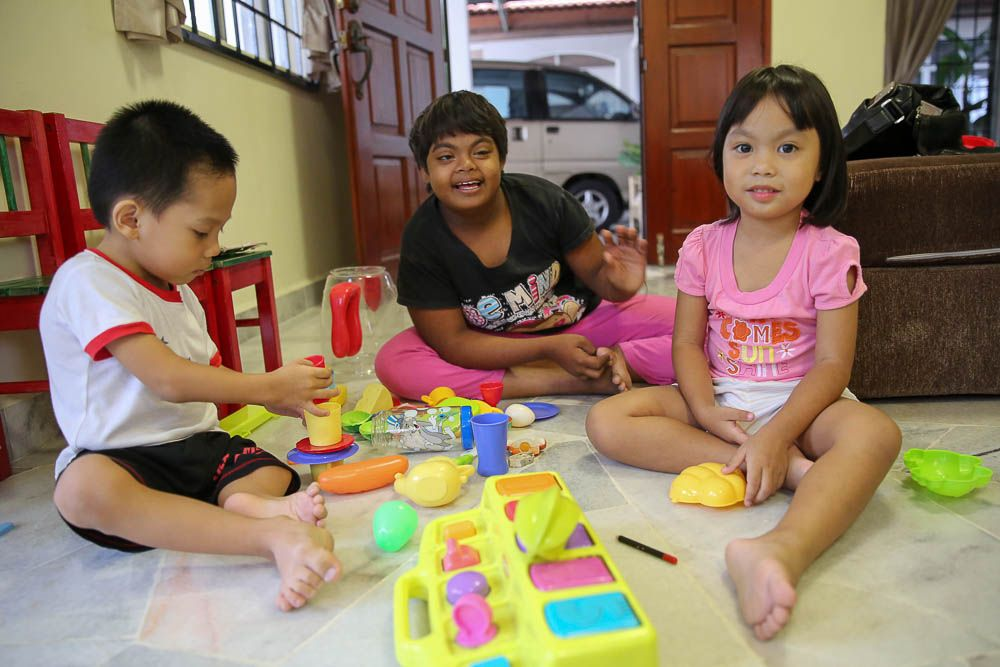 Isaac, Abigail and Isabella playing in their living room at Agape Home in Bukit Beruntung. — Picture by Choo Choy May