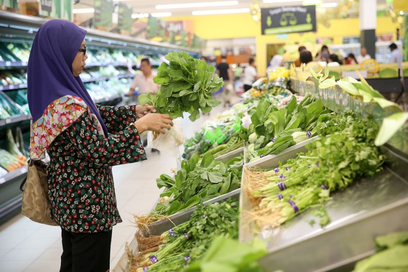 A shopper chooses fresh vegetables from the fresh produce section in Tesco. — Picture by Choo Choy May