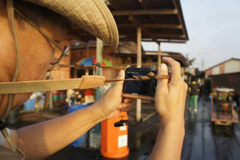 Maxby shows how to use the camera straps as a tripod. — Photos by Vivian Chong and Sasya Ahmad Sebi
