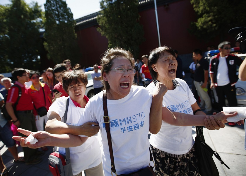 Family members of passengers onboard the missing Malaysia Airlines Flight MH370, cry as they gather to pray Yonghegong Lama Temple in Beijing September 8, 2014, on the six-month anniversary of the disappearance of the plane. — Reuters pic