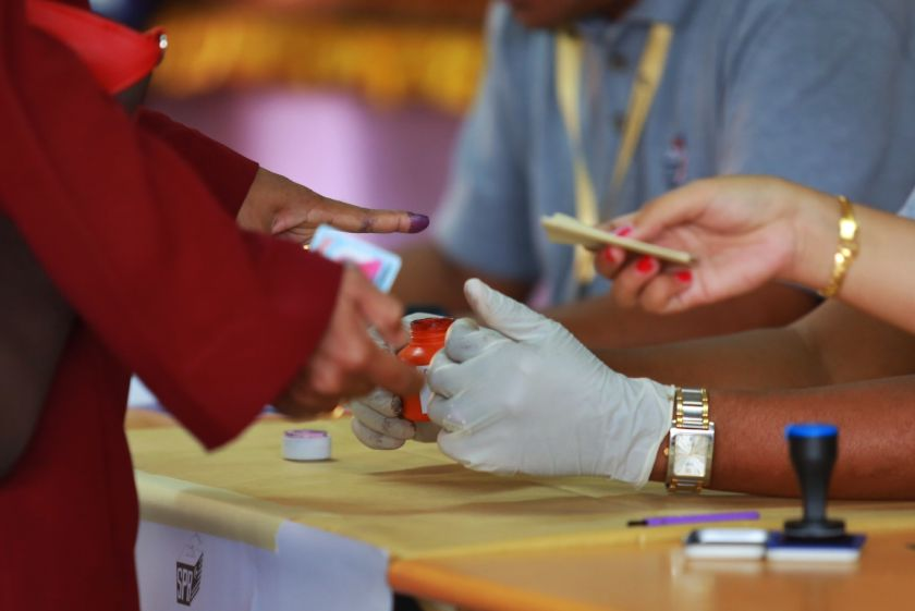 A Pengkalan Kubor constituent gets her finger inked before casting her ballot at a polling station, September 25, 2014. — Picture by Saw Siow Feng